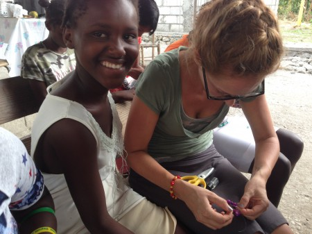 Miss Melissa helping the girls make bracelets for the teenage bible study.